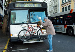 Person putting bike onto bus bike rack