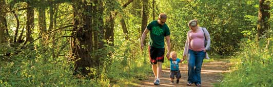 family walking in forest with son