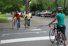 Cyclists walking across crosswalk