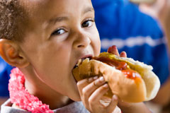 Photograph of boy eating hotdog