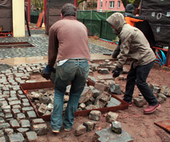 Students lay cobblestones on the plaza