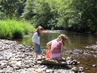 girls playing by a creek