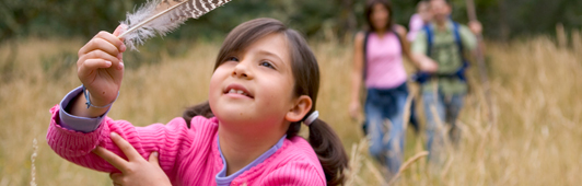 girl holding hawk feather